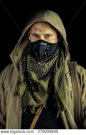 Man With Burglar Crowbar Wearing Black Protactive Face Mask And Jacket With Hood On Black Background
