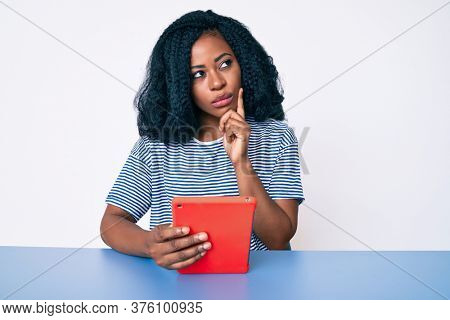 Beautiful african woman using touchpad device serious face thinking about question with hand on chin, thoughtful about confusing idea