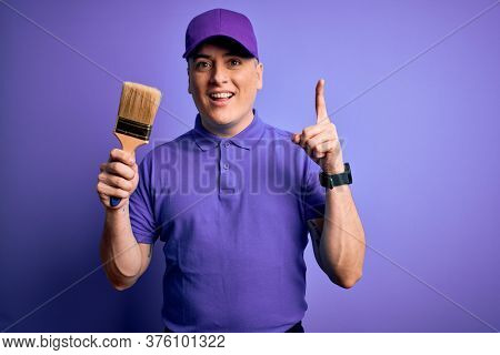 Young modern decorator painter man holding paint brush over purple background surprised with an idea or question pointing finger with happy face, number one