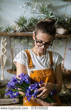 Surprised Florist Woman In Glasses, Wear Orange Overalls Surrounded By Collection Of Tillandsia Air