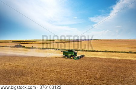Dobrich, Bulgaria - July 07, 2020: Modern John Deere Combine Harvesting Grain In The Field Near The