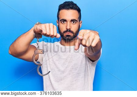 Young hispanic man holding prisoner handcuffs pointing with finger to the camera and to you, confident gesture looking serious