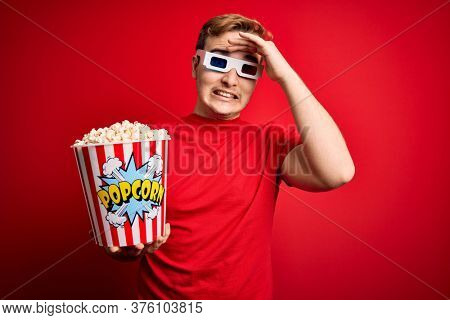 Young handsome redhead man watching 3d glasses eating popcorn snack over red background stressed with hand on head, shocked with shame and surprise face, angry and frustrated. Fear and upset
