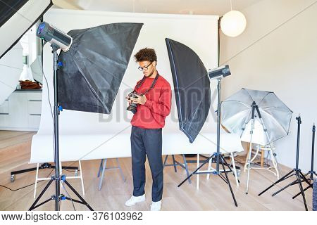 Photographer or photo student between studio lights in his photo studio