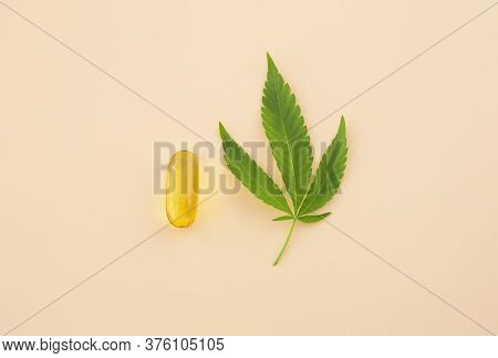 Hemp Extraction Oil In Medical Capsule And Cannabis Leaf On Light Background. Antiaging Beauty Conce