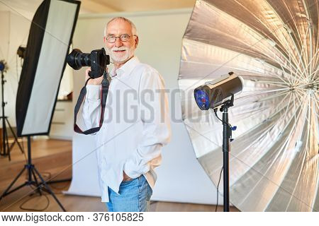 Cool freelance photographer with digital camera in front of a flash unit