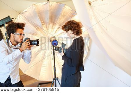 Photo students with different cameras in front of a flash unit in the studio