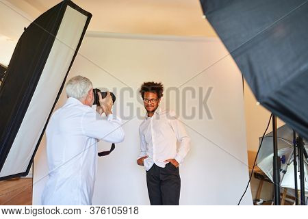Photographer photographs man as a model for portrait photos at the photo shoot