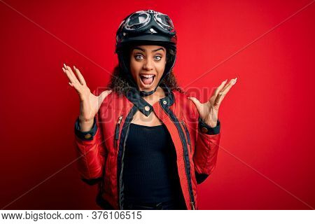Young african american motorcyclist girl wearing moto helmet and glasses over red background celebrating crazy and amazed for success with arms raised and open eyes screaming excited. Winner concept