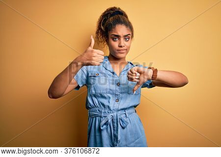 Young beautiful african american girl wearing denim dress standing over yellow background Doing thumbs up and down, disagreement and agreement expression. Crazy conflict