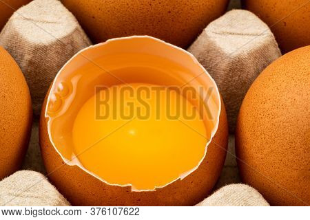 Half Broken Chicken Egg And Brown Chicken Eggs In Egg Carton On The Table. Eggs Are Loaded With Chol