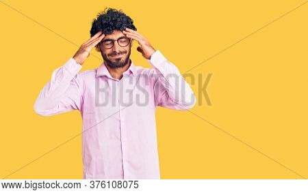 Handsome young man with curly hair and bear wearing business clothes with hand on head for pain in head because stress. suffering migraine.