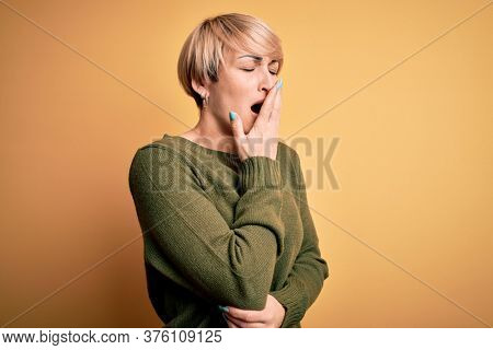 Young blonde woman with modern short hair wearing casual sweater over yellow background bored yawning tired covering mouth with hand. Restless and sleepiness.