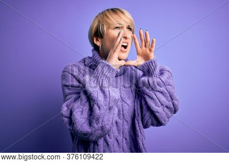 Young blonde woman with short hair wearing winter turtleneck sweater over purple background Shouting angry out loud with hands over mouth