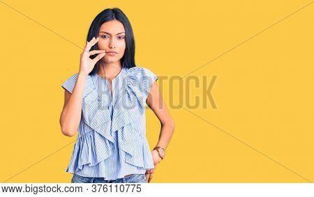 Young beautiful latin girl wearing casual clothes mouth and lips shut as zip with fingers. secret and silent, taboo talking