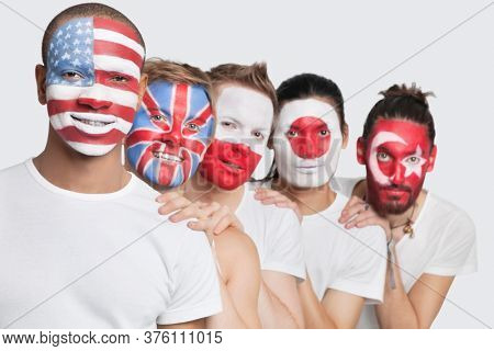 Portrait of Multi-ethnic group of male friends with various national flags painted on their faces standing against white background