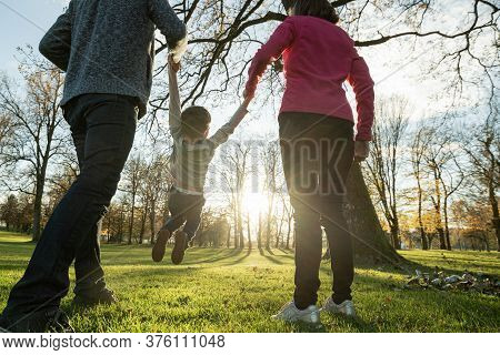 View From Behind Of Young Parents Holding Their Sons Hands Lifting Him In A Playful Image As They Wa
