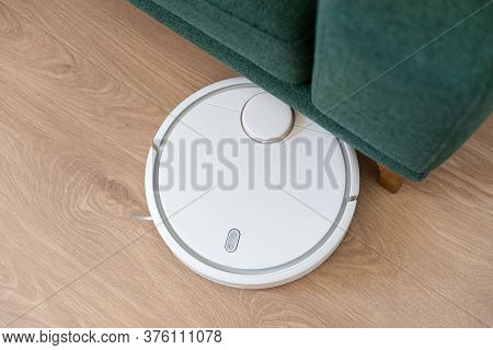 Housework And Technology Concept - Robotic Vacuum Cleaner Cleaning The Living Room Under The Sofa. H