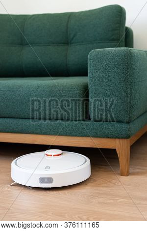 Robotic Vacuum Cleaner Cleaning The Livingroom Under The Green Sofa. Housekeeping Help, New Technolo