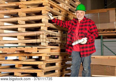 Middle aged working standing in front of wooden pallets