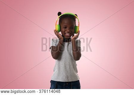 Music, Childhood And Technology Concept.lovely Happy Little Girl With Headphones Over Pink Backgroun