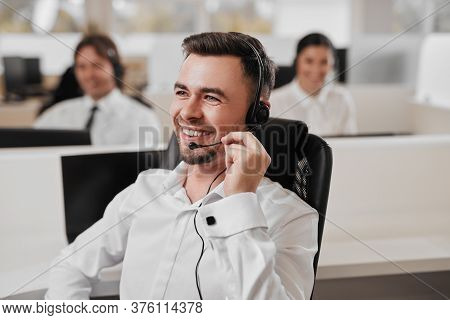 Positive Male Agent Smiling And Speaking With Customer Through Headset While Doing Telemarketing As