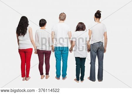 Back view of young multi-ethnic friends in casuals holding hands over white background