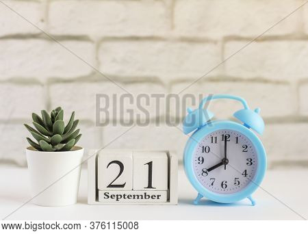 September 21 On A Wooden Calendar Next To The Alarm Clock.september Day, Empty Space For Text.calend