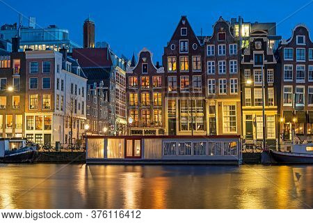 Amsterdam houses and house boats along the Amstel in Amsterdam the Netherlands at sunset