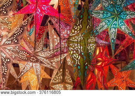 Group Colorful Seasonal Xmas Lantern Stars At Christmas Market. Traditional Shopping Decoration At X
