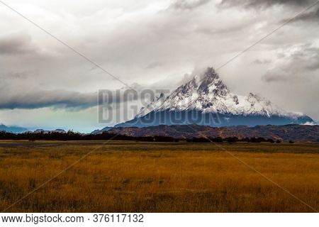 Peaked snow-capped mountain peak in the clouds. The amazing park of Torres del Paine. Extreme travel to Patagonia. The concept of photo and extreme tourism