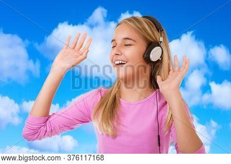 Happy Singing Teenage Girl With Headphones Over Blue Sky Background