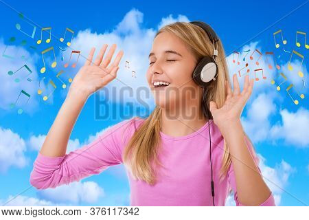 Happy Singing Teenage Girl With Headphones Over Blue Sky Background With Musical Notes
