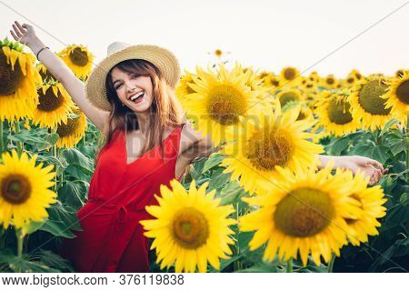 Happy Woman With Red Dress And Hat In Field Of Sunflowers