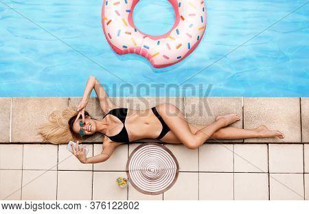 Top View Of Beautiful Young Girl In Bikini Taking Selfie While Lying At Poolside