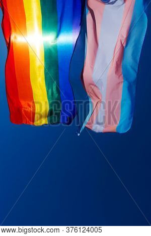 closeup of a gay pride flag and a transgender pride flag waving on the blue sky, moved by the wind, with the sun in the background and some blank space on the bottom