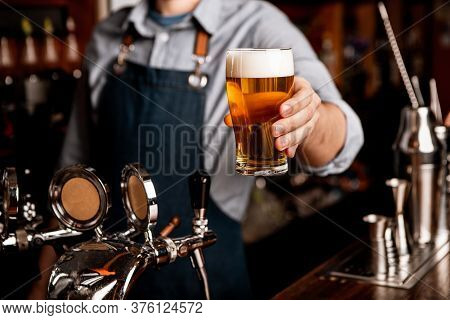 Brewer And Bartender In Pub. Man In Apron Gives Glass Of Light Beer With Foam In Interior Of Pub, Cr