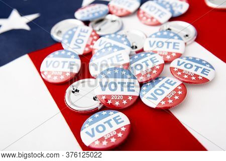 Vote 2020. Patriotic Pile Of Button Pins On Us Flag Background, Copy Space