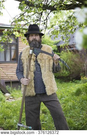 Adult Man With A Beard And A Hat In The Village In Summer, Posing At His Home With A Scythe For Haym