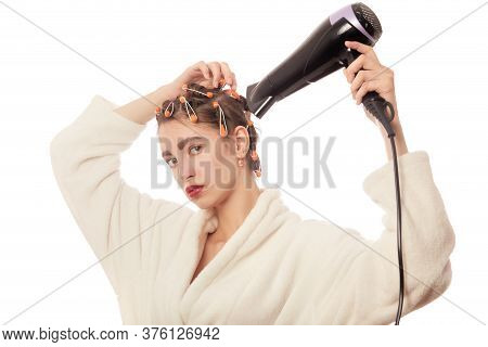 Young Woman In Bathrobe Drying Her Hair With Curlers On Head, Isolated On White Background