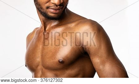 Sporty Black Bodybuilder Posing Standing In Studio On White Background. Building Chest Muscles Conce