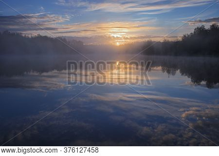 Dawn Over A Foggy Lake In The Forest Early In The Morning. Blue Sky And Sun Reflected In Water