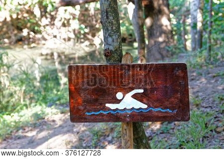 Wooden Hand Made Sign, Swimming Allowed, In A Forest Near River And Stream. Cooling Down On A Tropic