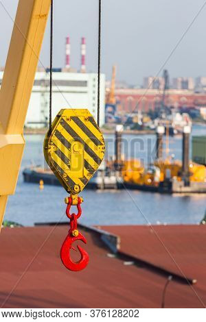 Loading Crane With Crook. Port Unloading Equipment. Industrial Work. Red Hook Close Up.