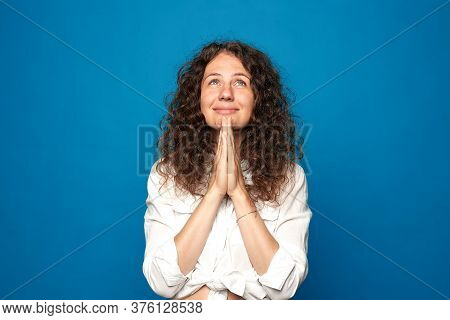 Positive Wishful Young Curly Haired Woman Keeps Palms Pressed Together, Hopes Dreams Come True, Make