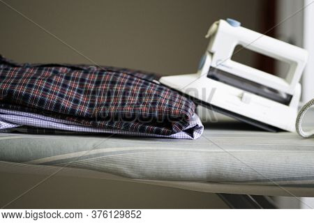 Freshly Ironed And Folded Shirts With An Electric Iron On An Ironing Board Table