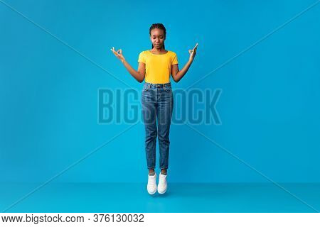Meditation. Peaceful African American Millennial Girl Meditating In Mid-air With Eyes Closed Over Bl