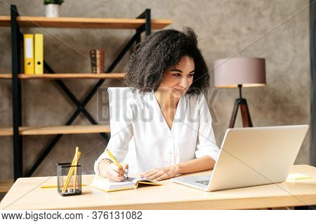 Concentrated African-american Young Woman In Smart Casual Wear Looks At The Laptop Screen While Sitt