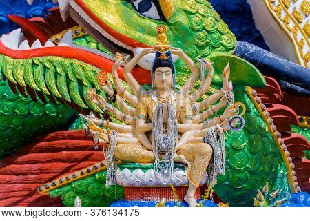 Religious Statue In A Buddhist Temple In Thailand. Statue Of A Multi-armed God With Offerings On The