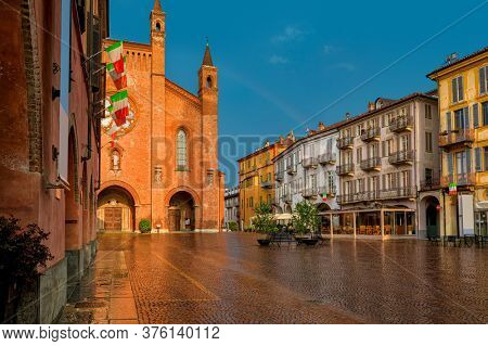 Wet cobblestone town square, old houses and San Lorenzo cathedral lit by sunlight under rainy sky in Alba, Piedmont, Northern Italy.